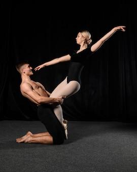 Mulher de balé e homem posando em collant