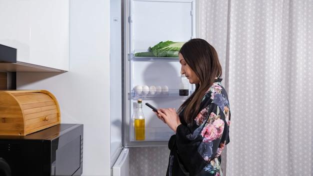 Mulher de bata abre a porta da geladeira para verificar os produtos