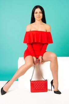 Mulher de belas pernas com vestido vermelho e bolsa de mão com sapatos de salto alto sentada no banco branco - imagem