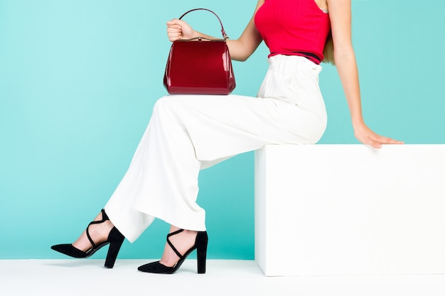 Mulher de belas pernas sentada no banco. com bolsa vermelha e sapatos de salto alto