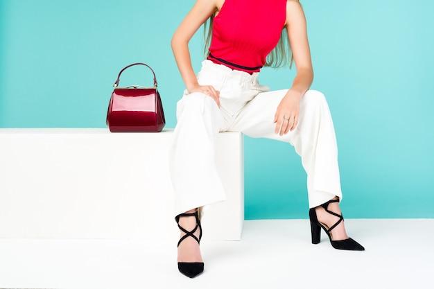 Mulher de belas pernas sentada no banco. com bolsa vermelha e sapatos de salto alto.