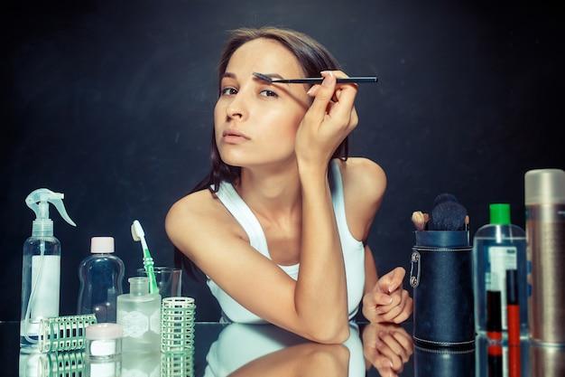 Mulher de beleza aplicando maquiagem. linda garota olhando no espelho e aplicando cosméticos com um pincel. bom dia, maquiagem e conceito de emoções humanas. modelo caucasiana em estúdio