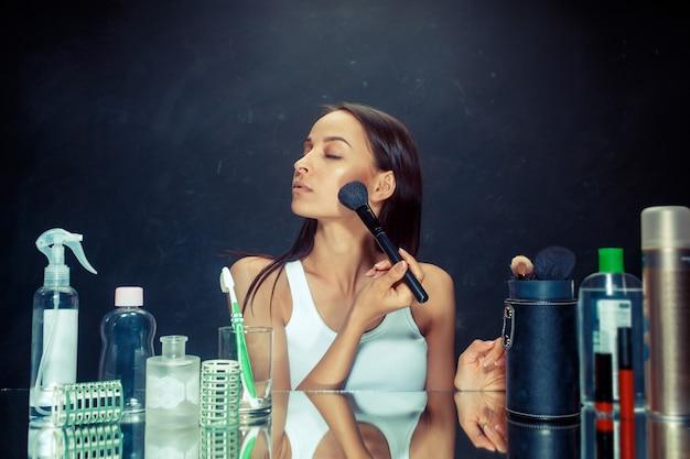 Mulher de beleza aplicando maquiagem. linda garota olhando no espelho e aplicando cosméticos com um pincel grande. bom dia, maquiagem e conceito de emoções humanas. modelo caucasiana em estúdio