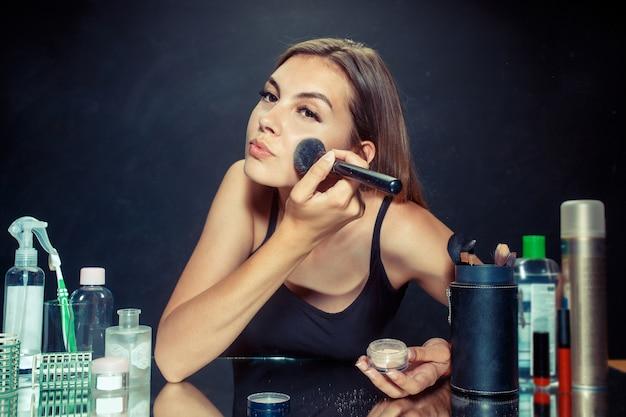 Mulher de beleza aplicando maquiagem. linda garota olhando no espelho e aplicando cosméticos com um pincel grande.