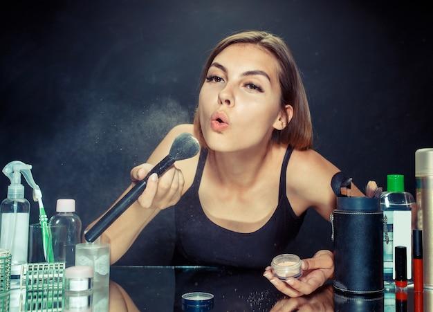 Mulher de beleza aplicando maquiagem. linda garota olhando no espelho e aplicando cosméticos com um pincel grande