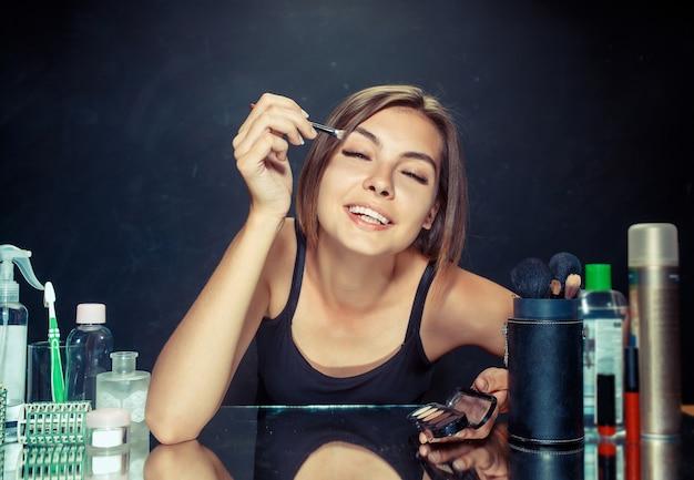 Mulher de beleza aplicando maquiagem. linda garota olhando no espelho e aplicando cosméticos com uma escova