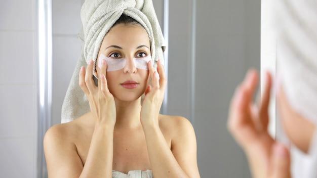 Mulher de beleza aplicando máscara antifadiga sob os olhos, olhando-se no espelho no banheiro.