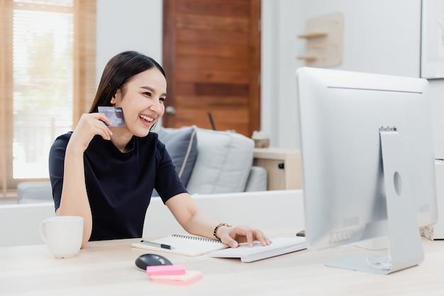 Mulher de beleza asiática usa cartão de crédito para fazer compras usando um computador através da internet com um rosto feliz e sorridente, sendo um novo negócio online normal na experiência de compras em casa.