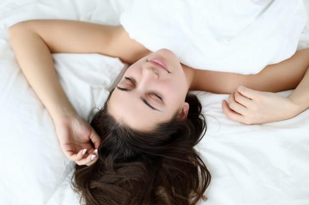 Mulher de beleza caucasiano jovem dormindo na cama branca