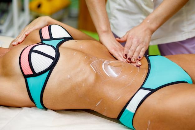 Mulher de beleza com massagem abdominal com creme no spa