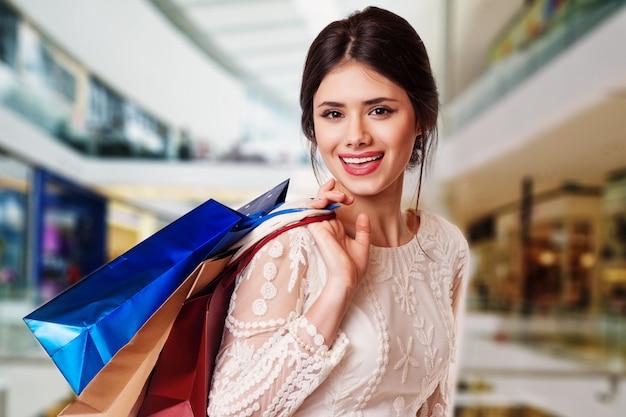 Mulher de beleza com sacos de compras no centro comercial.