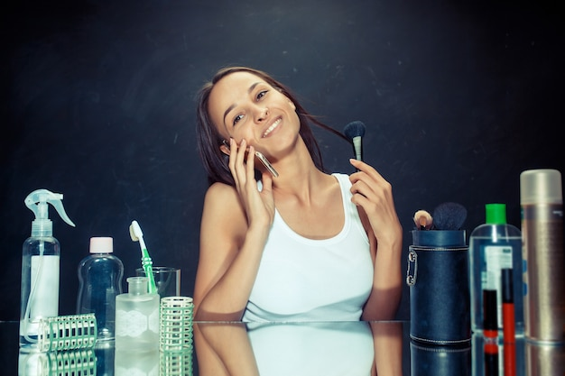 Mulher de beleza com telefone móvel, aplicar maquiagem. linda garota olhando no espelho e aplicando cosméticos com um pincel grande. bom dia, maquiagem e conceito de emoções humanas. modelo caucasiana em estúdio
