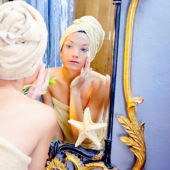 Mulher de beleza com toalha olhando no espelho dourado
