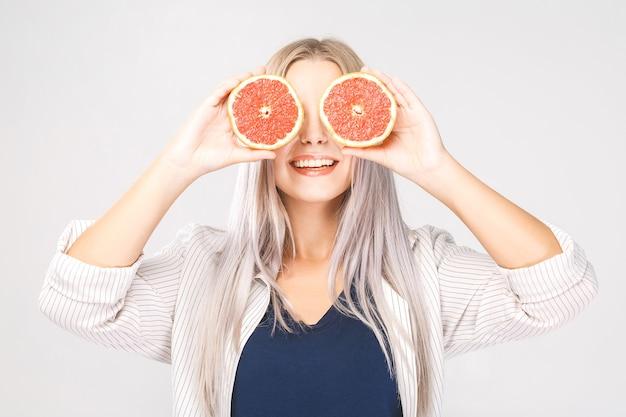 Mulher de beleza com toranja cítrica laranja com corpo de pele saudável. vitamina fresca atraente. isolado sobre o branco.