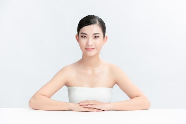 Mulher de beleza de skincare de rosto lindo isolada na parede branca. modelo de beleza asiática