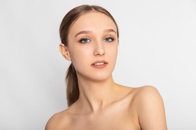 Mulher de beleza feliz olhando para longe, isolada no fundo. jovem morena alegre com ombro nu sorrindo após tratamento de pele. linda garota hispânica esperando terapia de spa.