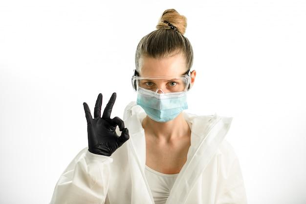 Mulher de beleza jovem em traje de proteção com óculos e luvas mostrando sinal okey
