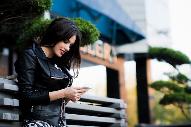 Mulher de beleza jovem escrever mensagem no celular em um café de rua.