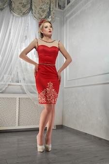 Mulher de beleza jovem, mulher magnífica no vestido vermelho, nas colinas, ha