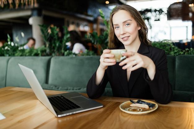 Mulher de beleza jovem no refeitório fala no telefone com o laptop e bebe café.