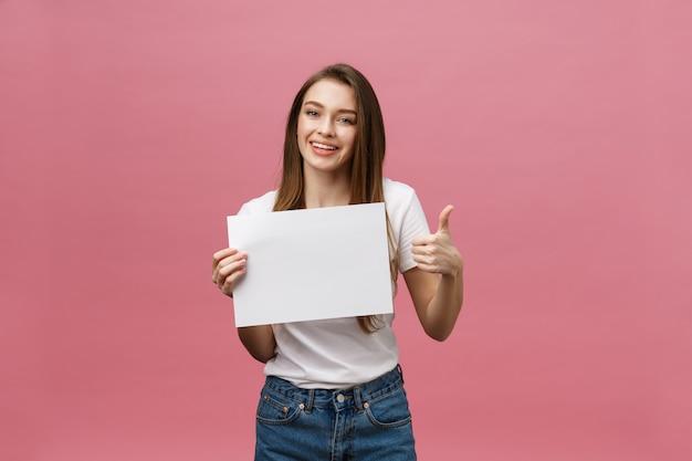 Mulher de beleza jovem segura cartão em branco e mostrando os polegares para cima sobre fundo rosa