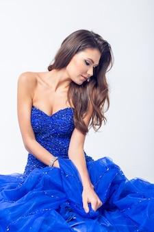 Mulher de beleza jovem tremulando vestido azul em uma parede branca