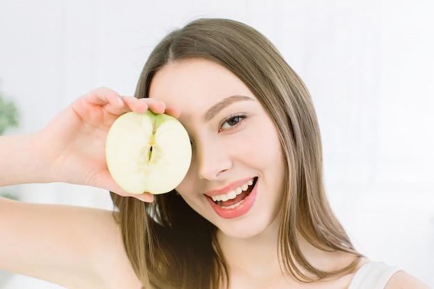 Mulher de beleza sorridente segurando metade da maçã verde. a menina fecha um olho com metade de uma maçã.