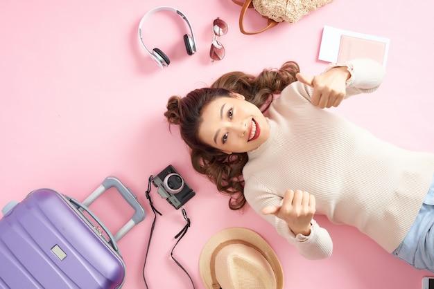 Mulher de beleza sorrir feliz e aparecer o polegar para você no chão rosa. deitada com sua bagagem de viagem