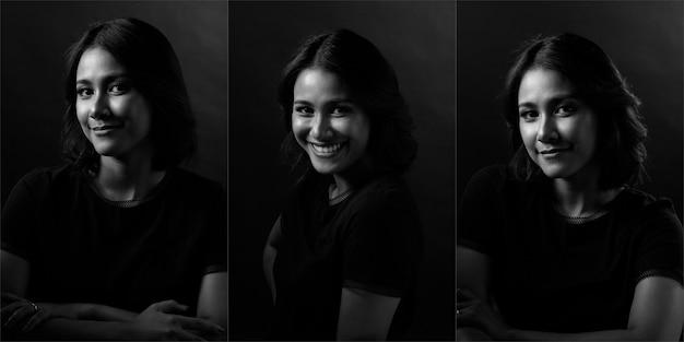 Mulher de beleza tem cabelo preto liso e expressa um sorriso de felicidade e sentimento. menina asiática mostra expressão de olhos no rosto sobre fundo escuro, retrato meio corpo monótono