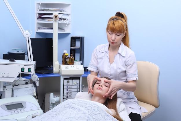Mulher de beleza tendo uma massagem cosmética, tratamento facial, close-up.
