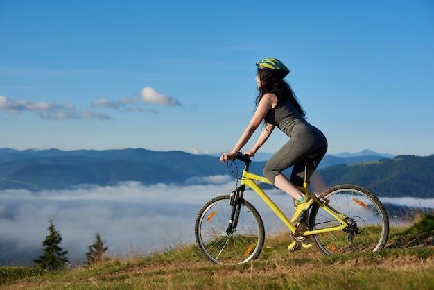 Mulher de bicicleta na bicicleta amarela