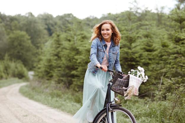 Mulher de bicicleta na floresta