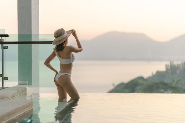 Mulher de biquíni branco andando em pose perto da piscina com a varanda de vidro transparente e vista para o mar.