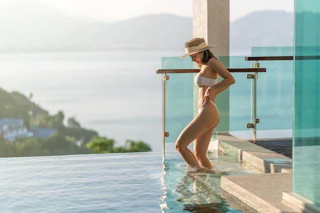 Mulher de biquíni branco entrando na piscina com a varanda de vidro transparente e vista para o mar.