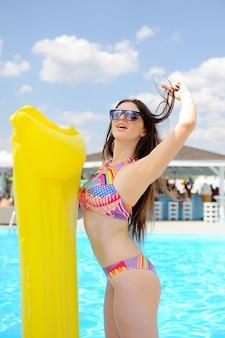 Mulher de biquíni com um colchão inflável amarelo