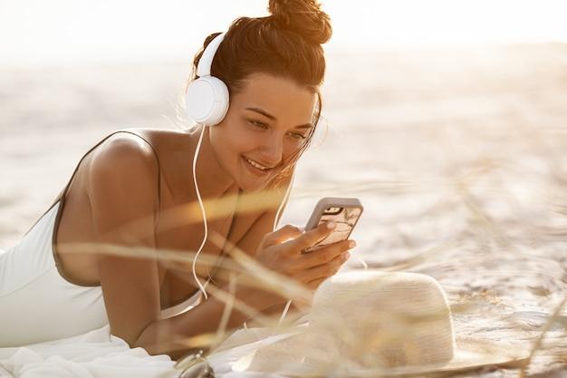 Mulher de biquíni com um smartphone e fones de ouvido na praia