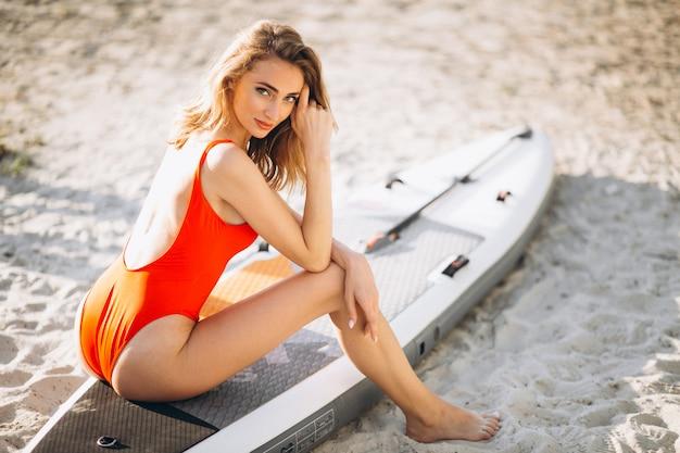 Mulher de biquíni com uma prancha de surf na praia ele