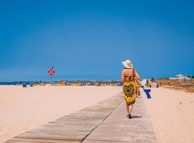 Mulher de biquíni e chapéu caminhando na praia