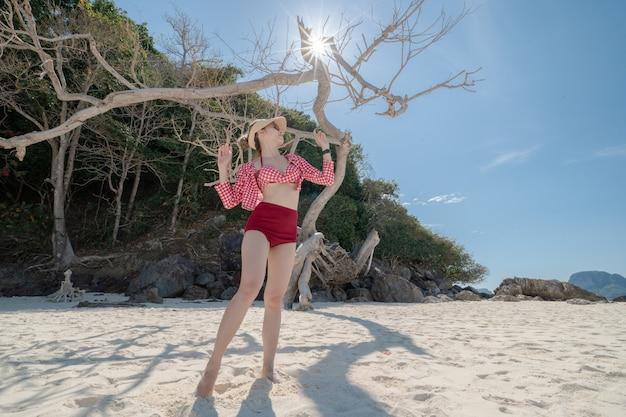 Mulher de biquíni em pé na praia de areia branca. paisagem azul do mar e do céu. férias de verão.