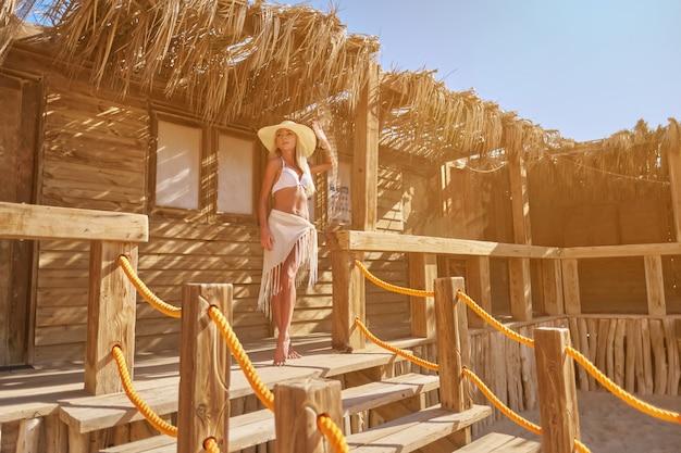 Mulher de biquíni em pé numa espreguiçadeira sob o dossel de palha na piscina do resort