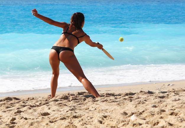 Mulher de biquíni jogando tênis em uma praia arenosa