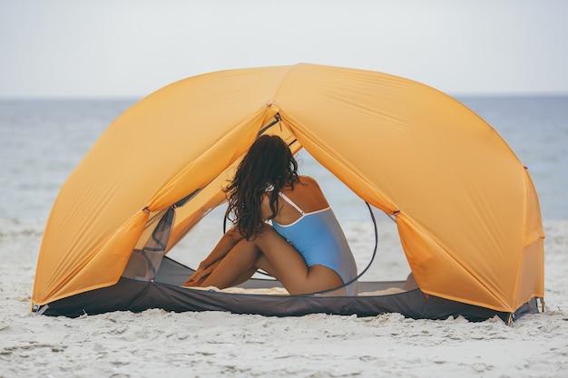 Mulher de biquíni na praia em uma barraca