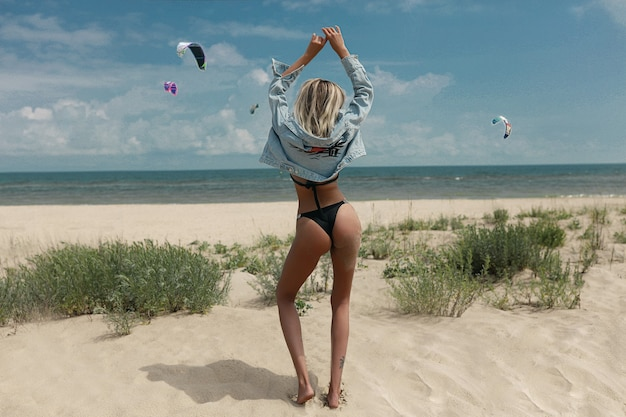 Mulher de biquíni preto com cabelo molhado na praia ao pôr do sol