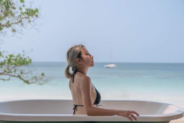 Mulher de biquíni preto relaxando na banheira com a praia do oceano.