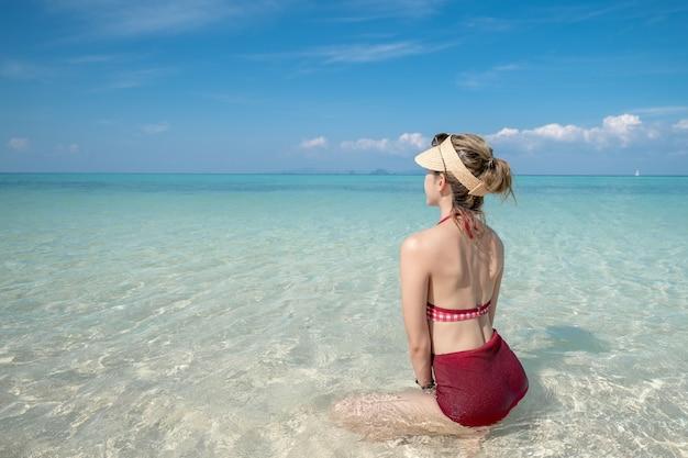 Mulher de biquíni sentada na água do mar, na praia de areia branca. paisagem azul do mar e do céu. férias de verão.