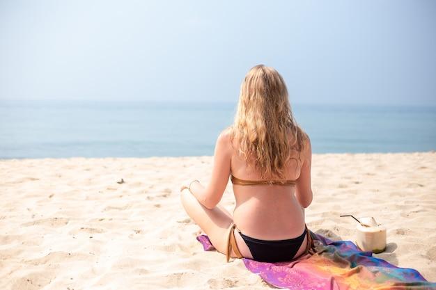 Mulher de biquíni sentada na areia na praia em posição de lótus