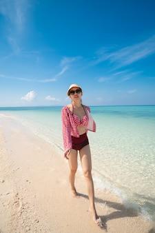 Mulher de biquíni vermelho andando na praia de areia, garota feliz, desfrutando na praia.