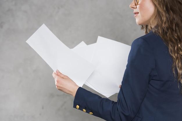 Mulher de blazer segurando papéis