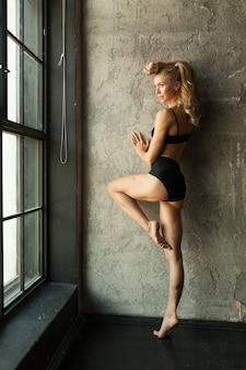 Mulher de blondie de aptidão em pé perto da parede e janela