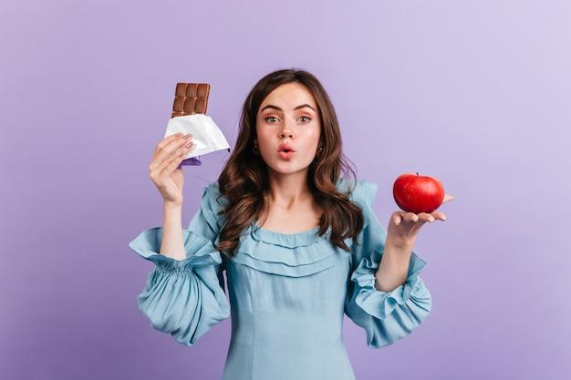 Mulher de blusa azul está posando na parede roxa. garota atraente pensa em sua dieta, escolhendo entre maçã suculenta e chocolate gordo.